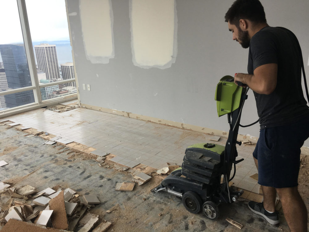 Process of removal of glued engineered flooring for the purpose of replacement with a new one. High rise building in San Francisco.